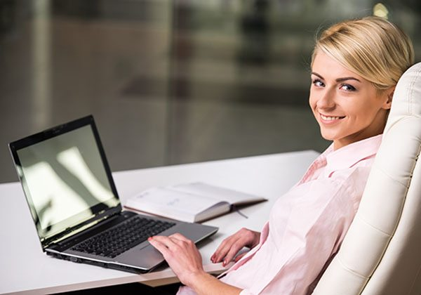 Side view of smiling businesswoman is working at office.